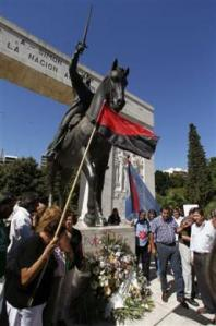 Supporters of Venezuela's late President Hugo Chavez stand at the memorial of Venezuelan hero Simon Bolivar during a ceremony to pay homage to Chavez in Buenos Aires