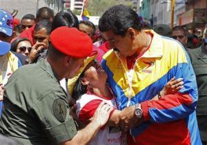 Venezuela's Vice President Nicolas Maduro consoles a supporter of deceased Venezuelan leader Hugo Chavez in Caracas