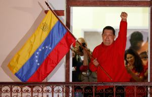 Venezuelan President Hugo Chavez waves the national flag while celebrating from a balcony at Miraflores Palace in Caracas