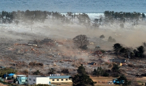Houses are swept by a tsunami in Natori City in northeastern Japan