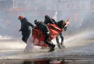 Demonstrators try to protect themselves with a banner as riot police use water cannons to disperse them during a protest in Ankara