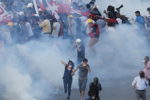 Protesters run as riot police fire teargas during a protest at Taksim Square