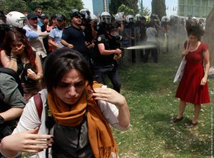 Turkish riot policeman uses tear gas during a protest in central Istanbul