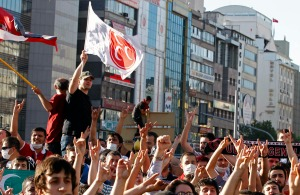 Supporters of Nationalist Movement Party make grey wolf sign of party and shout slogans as one waves a party flag during a protest in central Ankara