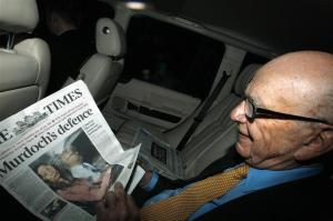 News Corp Chief Executive and Chairman Rupert Murdoch holds a copy of The Times newspaper as he leaves his home in London