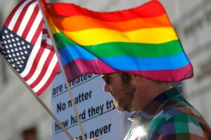 A man carries flags at a rally in support of same-sex marriage at the State of California Supreme Court in San Francisco