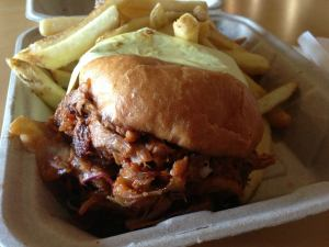 Pulled pork sandwich with honey chipotle glaze, grilled onion, jalapeno slaw and fries_n