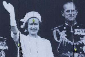Abseilers secure a giant canvas along the River Thames of a photograph showing Britain's Royal Family during the 1977 Silver Jubilee