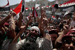 Anti-government protesters spray foam and wave the national flag as they celebrate Yemeni President Ali Abdullah Saleh's departure to Saudi Arabia, in Sanaa