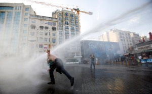 Turkish riot police use water cannon to disperse demonstrators during a protest against the destruction of trees in a park brought about by a pedestrian project, in Taksim Square in central Istanbul