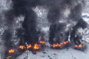 Smoke from burning tyres set ablaze by pro-European protesters rises during clashes with riot police in Kiev
