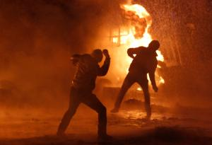 Demonstrators throw objects towards riot police during a rally held by pro-European protesters in Kiev