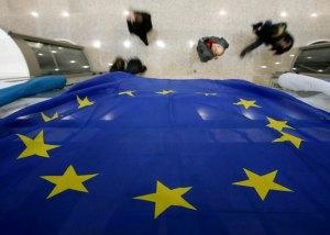 People walk in EU Council's media room in Brussels