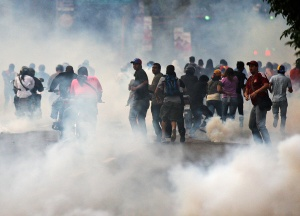 Supporters of opposition leader Henrique Capriles run from tear gas fired by riot police in Caracas