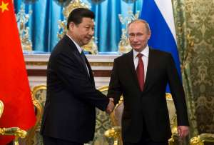 Russia's President Putin shakes hands with his Chinese counterpart Xi in Moscow