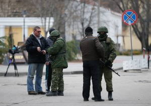 Armed men check journalists documents around the regional parliament building in the Crimean city of Simferopol