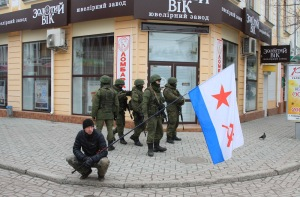 Armed men patrol as a man holds a Soviet Navy flag in the centre of the Crimean city of Simferopol