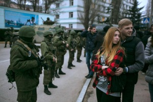 A couple stands next to armed servicemen outside a Ukrainian border guard post in the Crimean town of Balaclava
