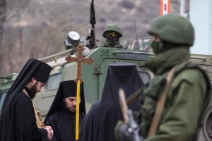 Orthodox monks pray next to armed servicemen near Russian army vehicles outside a Ukrainian border guard post in the Crimean town of Balaclava
