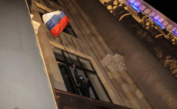 A pro-Russian protester waves Russian flag as he looks out of a window of seized regional administrative building in Kharkiv