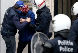 Injured demonstrator is helped by riot police officers during a European trade unions protest against austerity measures, in central Brussels
