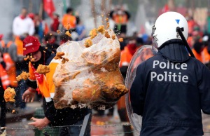 Demonstrator throws garbage towards riot police officers during a European trade unions protest against austerity measures, in central Brussels