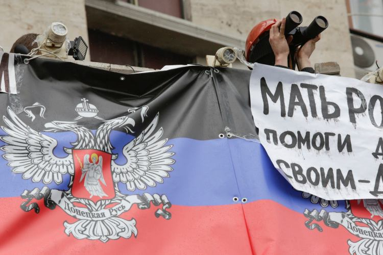 A pro-Russia protester looks through a pair of binoculars as he stands atop the entrance to a regional government building in Donetsk