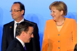 British Prime Minister David Cameron passes in front of French President Francois Hollande and German Chancellor Angela Merkel during the family picture of the NATO Summit in Chicago