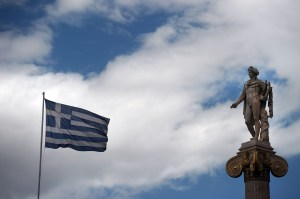 "A Greek flag waves next to a statue of the Greek ancient god Apollo in Athens on 23 May, 2012. IMF chief Christine Lagarde warned on Wednesday of the risk of ""contamination"" if Greece quits the euro and said the eurozone might therefore see the value of paying more to keep Greece in. AFP PHOTO / ARIS MESSINIS"