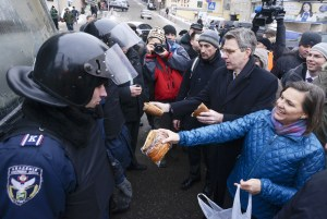 A handout picture released on December 10, 2013 by Ukrainian Union Opposition press services hows US Assistant secretary of State for European and Eurasian Affairs Victoria Nuland (R) distributing cakes to riot policemen on the Independence Square in Kiev on December 10, 2013.  AFP PHOTO/ ANDREW KRAVCHENKO