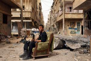 "A member of the Free Syrian Army holds his weapon as he sits on a sofa in the middle of a street in Deir al-Zor, in this April 2, 2013 file photo. The United States believes with varying degrees of confidence that Syria's regime has used chemical weapons on a small scale, the White House said on Thursday. But it added that President Barack Obama needed ""credible and corroborated"" facts before acting on that assessment  REUTERS/Khalil Ashawi/Files  (SYRIA - Tags: CIVIL UNREST CONFLICT)"