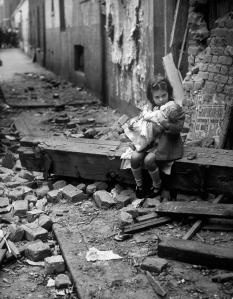 1940:  A little girl holding her doll in the rubble of her bomb damaged home.  (Photo by Fox Photos/Getty Images)