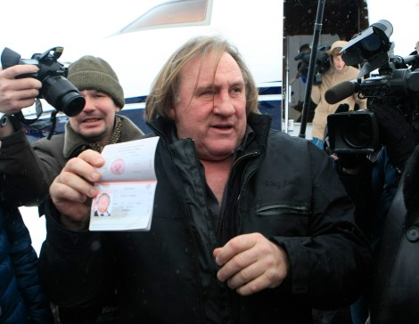 French film star Gerard Depardieu shows his passport after arriving at the airport in the town of Saransk in the Mordoviya Republic, southeast of Moscow, January 6, 2013. Depardieu received a hug from Russia's President Vladimir Putin and a new Russian passport on Sunday after abandoning his homeland to avoid a new tax rate for millionaires. REUTERS/Yulia Chestnova (RUSSIA - Tags: ENTERTAINMENT POLITICS SOCIETY IMMIGRATION)