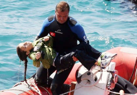 A diver carries a young girl, after a boat carrying illegal immigrants trying to reach Europe capsized in waters off western Turkey, on September 6, 2012 near Izmir. Forty-five people including two crew members were rescued alive, and at least 39 people drowned. The captain and his maid who were among the survivors were detained. AFP PHOTO / IHLAS NEWS AGENCY **TURKEY OUT**