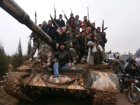 Free Syrian Army fighters pose on a tank, which they say was captured from the Syrian army loyal to President Bashar al-Assad, after clashes in Qasseer, near Homs November 19, 2012. Picture taken November 19, 2012. REUTERS/Shaam News Network/Handout (SYRIA - Tags: POLITICS CIVIL UNREST) FOR EDITORIAL USE ONLY. NOT FOR SALE FOR MARKETING OR ADVERTISING CAMPAIGNS. THIS IMAGE HAS BEEN SUPPLIED BY A THIRD PARTY. IT IS DISTRIBUTED, EXACTLY AS RECEIVED BY REUTERS, AS A SERVICE TO CLIENTS ORG XMIT: AMM33