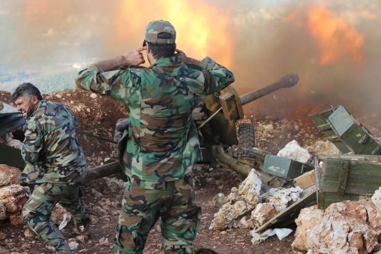 In this photo taken on Saturday, Oct. 10, 2015, Syrian army personnel fire a cannon in Latakia province, about 12 from the border with Turkey in Syria. Backed by Russian airstrikes, the Syrian army has launched an offensive in central and northwestern regions. (Alexander Kots/Komsomolskaya Pravda via AP)