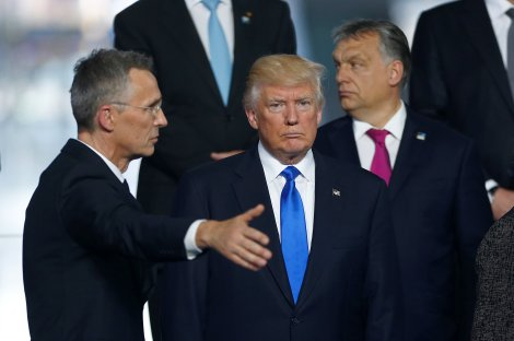 NATO Secretary General Jens Stoltenberg directs U.S President Donald Trump who takes his place as NATO member leaders gather before the start of their summit in Brussels
